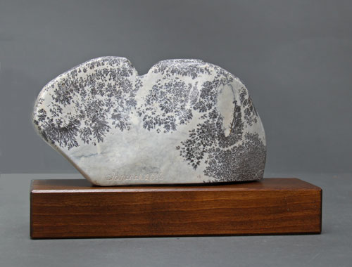A view of the back of dendritic Soapstone Owl #20 by Clarence P. Cameron of Madison, Wisconsin